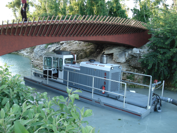 Portable, self propelled, steerable Rotomite-6000 dredge moving up canal.