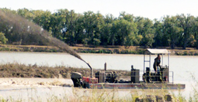 Portable, shallow draft Rotomite-SD110 side-casting dredged materials.